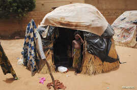 "FILE - A girl stands outside a hut in Niger's capital, Niamey. In impoverished Niger, recurring and more intense drought ""is absolutely punishing,"" a U.N. official says."