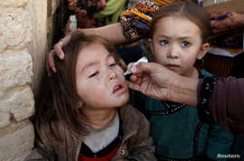 A girl receives polio vaccine drops from a vaccination worker outside her family home in Quetta, Pakistan Jan. 2, 2017.