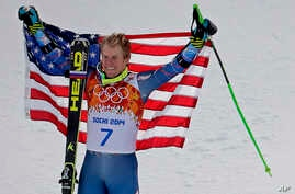 Men's giant slalom gold medalist Ted Ligety of the United States poses for photographers on the podium at the Sochi 2014 Winter Olympics, in Krasnaya Polyana, Russia, Feb. 19, 2014.