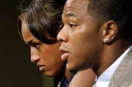 FILE - Janay Rice, left, looks on as her husband, Baltimore Ravens running back Ray Rice, speaks to the media during a news conference in Owings Mills, Md.
