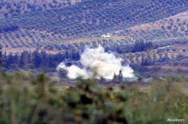 Smoke rises after a mortar bomb fired from Syria landed on Turkish soil on the Turkish-Syrian border in southern Hatay province, October 8, 2012.