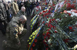 """People attend a commemoration ceremony at the monument of the so-called """"Nebesna Sotnya"""" (Heavenly Hundred), the anti-government protesters killed during the Ukrainian pro-European Union (EU) mass protests in 2014, during a rally marking the third an"""