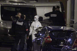 French police and forensic investigators stand outside the offices of French  satirical weekly Charlie Hebdo in Paris, Jan. 7, 2015, after armed gunmen stormed the offices leaving 12 dead.