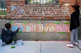 Two boys help finish a chalk mural at Marshall Field Garden Apartments during the Art on Sedgwick annual art show in Chicago, June 1, 2018.
