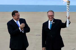 Rio 2016 organizing committee president Carlos Nuzman, right, holds a torch with the Olympic Flame as the head of Greece's Olympic Committee, Spyros Capralos applauds during the handover ceremony at Panathinean stadium in Athens on April 27, 2016.