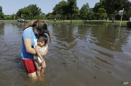 Gabby Aviles carries her daughter Audrey through floodwaters outside their apartment in Houston, Texas, May 26, 2015.