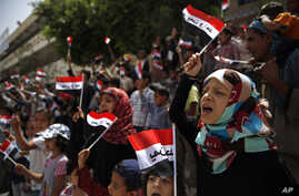 """Yemeni children chant slogans and wave Yemeni flags that read """"Yemen one"""" in Arabic, during a protest in Sana'a against Saudi-led airstrikes in Yemen, June 6, 2015."""