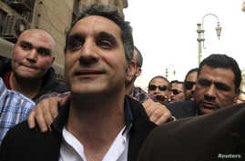 Bassem Youssef (C), the country's best-known satirist, gestures to journalists and activists as he arrives at the high court to appear at the prosecutor's office in Cairo Mar. 31, 2013.