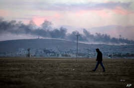A Turkish Kurd walks on the outskirts of Suruc, at the Turkey-Syria border, as smoke from an airstrike rises over Kobani, Syria, as fighting intensifies between Syrian Kurds and the Islamic State group, Oct. 8, 2014.
