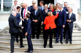FILE - German Chancellor Angela Merkel nad French President Emmanuel Macron arrive for a family photo before a meeting with the Franco-German Ministerial Council in Meseberg, Germany, June 19, 2018.