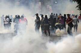 Supporters of opposition leader Henrique Capriles run from tear gas fired by riot police as they rally for an election recount, Caracas, April 15, 2013.