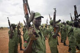FILE - South Sudanese rebel soldiers raise their weapons at a military camp in the capital Juba, South Sudan.