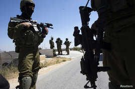 Israeli soldiers patrol during operation to locate three missing teenagers, in the West Bank city of Hebron, June 18, 2014.