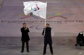 Chen Jining, mayor of Beijing waves the Paralympic flag after receiving it from Andrew Parsons, President of the International Paralympic Committee at the closing ceremony of the 2018 Winter Paralympics in Pyeongchang, South Korea, March 18, 2018.