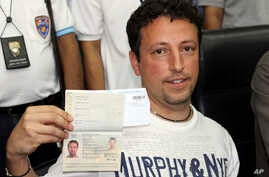 Italian Luigi Maraldi, left, whose stolen passport was used by a passenger boarding a missing Malaysian airliner, shows his passport as he reports himself to Thai police at Phuket police station in Phuket province, southern Thailand, March 9, 2014.
