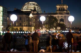 """People pass by balloons of the art project """"Lichtgrenze 2014"""" (""""Lightborder 2014""""), one of many events and displays in Berlin commemorating the fall of the Berlin Wall 25 years ago, Nov. 8, 2014."""
