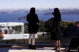 FILE - The Sydney Opera House and Harbour Bridge can be seen behind real estate agent LuLu Sun (R) as she escorts Bao Fang, a potential buyer from Shanghai, during an inspection of a property for sale in the Sydney suburb of Vaucluse, Australia, July