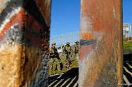 Agents with the U.S. Border Patrol Tactical Unit stand guard behind the border fence between Mexico and the United States, as seen from Tijuana, Mexico, Nov. 14, 2018.