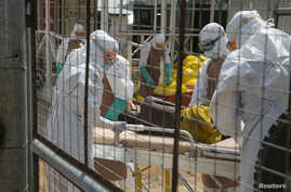 British health workers lift a newly admitted Ebola patient onto a wheeled stretcher in to the Kerry town Ebola treatment center outside Freetown, Sierra Leone, Dec. 22, 2014.