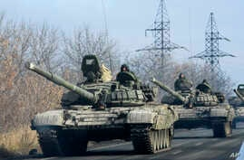 Pro-Russian rebel military vehicles convoy move towards Donetsk , Eastern Ukraine, Monday, Nov. 10, 2014. On Saturday, Associated Press reporters saw scores of military vehicles moving near Donetsk and farther to the east. Many of the unmarked vehicl...