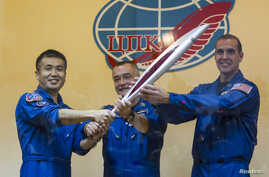 International Space Station (ISS) crew members, (L to R) Japanese astronaut Koichi Wakata, Russian cosmonaut Mikhail Tyurin and U.S. astronaut Rick Mastracchio, pose with the torch of the 2014 Sochi Winter Olympic Games after a news conference behind