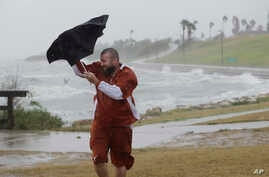Matt Looingvill struggles with his umbrella as he tries to walk in the wind and rain, Aug. 25, 2017, in Corpus Christi, Texas.