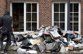 A member of a television crew is seen beside burnt files and documents in front of a building of German newspaper Hamburger Morgenpost in Hamburg, Germany, Jan. 11, 2015.