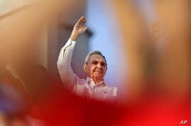 Cuba's President Raul Castro waves to workers as he watches the May Day march in Havana, Cuba, May 1, 2014.