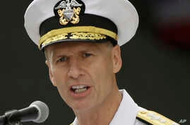 FILE - U.S. Navy Vice Adm. Joseph Aucoin, commander of the 7th Fleet, delivers a speech in front of the nuclear-powered aircraft carrier USS Ronald Reagan upon his arrival at the U.S. Navy base in Yokosuka, south of Tokyo.