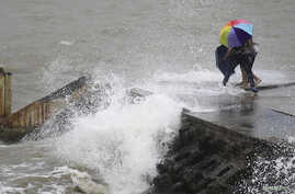 People move away as waves caused by Typhoon Utor crash on a seawall in Haikou, Hainan province, China, Aug. 14, 2013.