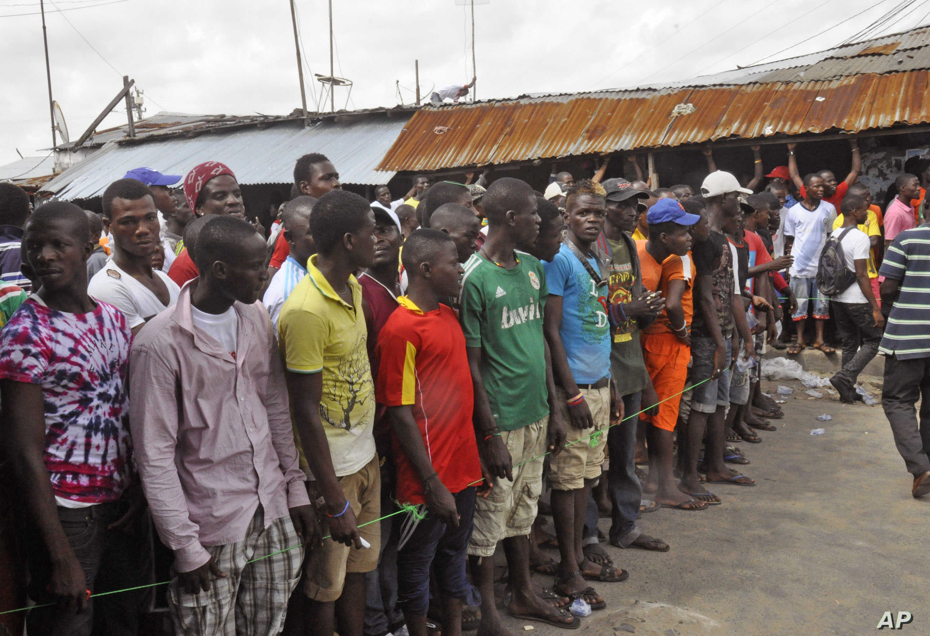 West Point residents stand behind a green string marking a holding area, as they wait for a second consignment of food from the Liberian Government to be handed out, at the West Point area, near the central city area of Monrovia, Liberia, Friday, Aug