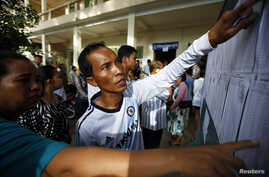 People look through the voters' list after a polling station opened for the general elections in Kandal province, Cambodia, July 28, 2013.