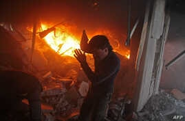 A Syrian man searches for people in a fire following regime air strikes on the rebel-held besieged town of Douma in the eastern Ghouta region, on the outskirts of the capital Damascus, Feb. 7, 2018.