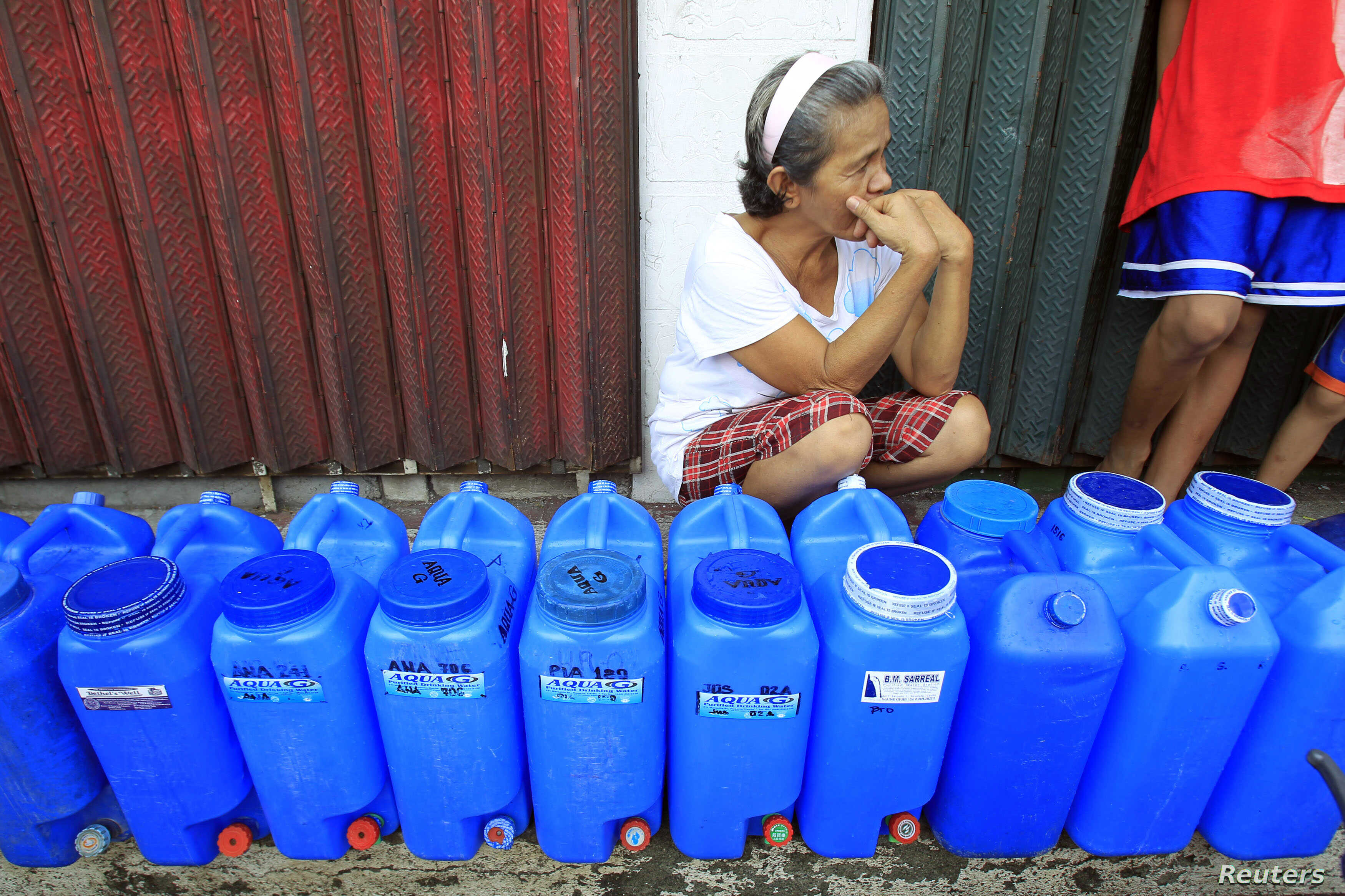 A resident queues with plastic containers to collect drinking water in Rosario, July 18, 2014.