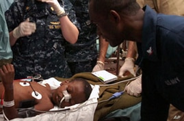 Medical professionals aboard the Military Sealift Command hospital ship USNS Comfort (T-AH 20) treat a six-year-old Haitian