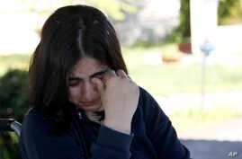 Fatima Bakhshi, a migrant from Afghanistan, cries in a small care home in the village of Doljevac, in southern Serbia, April 10, 2017.