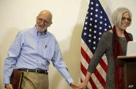 Alan Gross smiles as he walks in with his wife Judy before speaking to members of the media at his lawyer's office in Washington,  Dec. 17, 2014.
