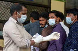 Indians standing in a queue outside a hospital wear masks as a precautionary measure against the Nipah virus at the Government Medical College hospital in Kozhikode, in the southern Indian state of Kerala, May 21, 2018.