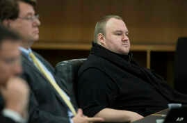 FILE - Kim Dotcom sits in the Auckland District Court during an extradition hearing in Auckland, New Zealand.
