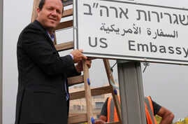 In this photo released by the Jerusalem Municipality, Jerusalem mayor Nir Barkat poses with a new road sign to the new U.S. Embassy in Jerusalem, Israel, May 7, 2018.
