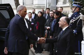 U.S. Attorney General Eric Holder (L) is welcomed by French Interior Minister Bernard Cazeneuve in Paris, France, Jan. 11, 2015.