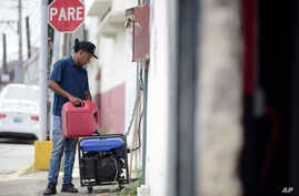 Juan Castro fills a power plant with gasoline to energize the cabinet building workshop where he works, in San Juan, Puerto Rico, April 18, 2018. Officials say it will take 24 to 36 hours to restore power after a blackout hit the entire island, nearl...