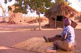 Women sit outside their huts on the outskirts of Harare, Zimbabwe. (Photo courtesy Human Rights Watch)