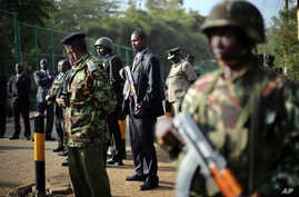 Kenyan security forces line up behind Interior Minister Joseph Ole Lenku during press conference near Westgate Mall, Nairobi, Sept. 25, 2013.
