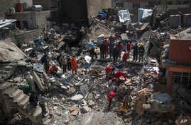 Civil protection rescue team work on the debris of a destroyed house to recover the bodies of people killed on the western side of Mosul, Iraq, March 24, 2017.