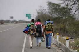 FILE - Venezuelan migrants walk to Lima along the shoulder of the Pan-American Highway near Tumbes, Peru, Aug. 26, 2018.