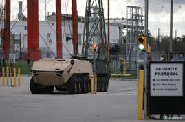 FILE - A pair of armored personnel carriers are parked on the grounds of the General Dynamics Land Systems - Canada factory in London, Ontario, Canada Oct. 23, 2018.