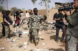 Malian soldier gestures at journalists to leave area of a French air strike in Konna, 430 miles north of Bamako, Jan. 26, 2013.