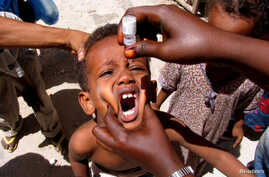 A health worker drops anti-polio vaccine into the mouth of a Somali child in the capital Mogadishu September 10, 2006. Health workers today began a polio immunisation drive in Kenya, Somalia and Ethiopia.   REUTERS/Shabelle Media (SOMALIA) - RTR1H6YV