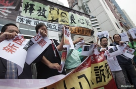"Pro-democracy lawmaker Lee Cheuk-yan (2nd L) and other protesters tear pieces of paper with a picture of the 18th Communist Party Congress, with a banner that reads, ""Release of political prisoners,"" outside the Chinese liaison office in Hong Kong,"